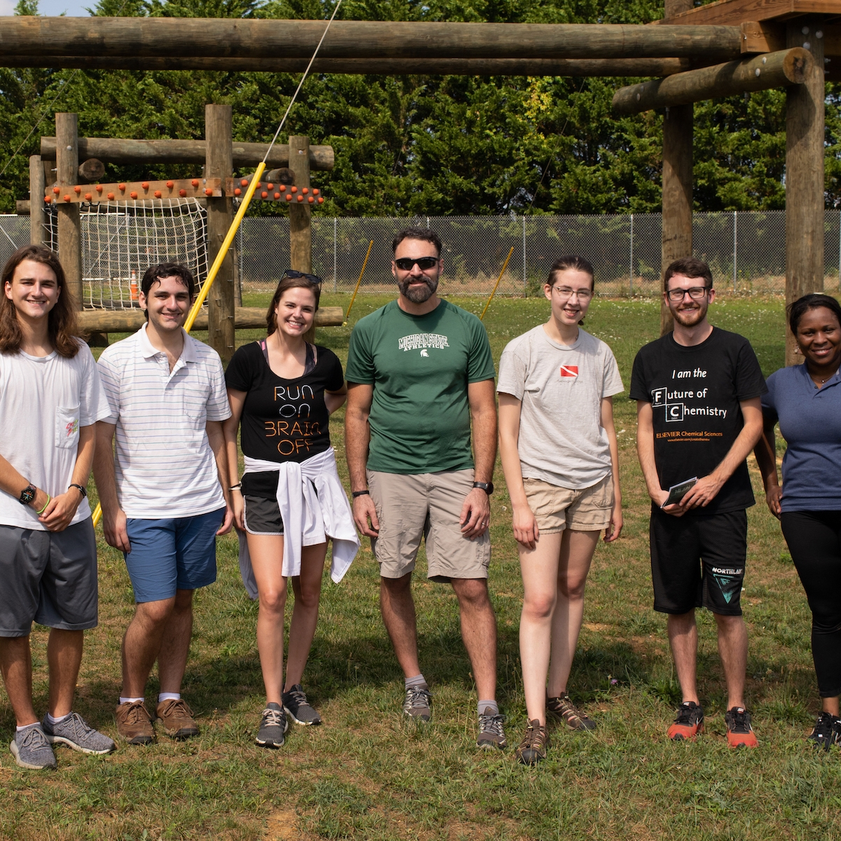 Six new macro students and two current macro students stand in front of the venture out ropes course at Virginia Tech.