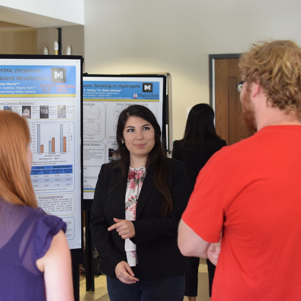 An R-E-U student shares her research with two people interested in her poster.