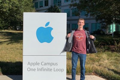 A young man wearing a black coat and maroon Hokies shirt stands next to a sign saying Apple Campus One Infinite Loop and the Apple logo . It is a sunny day with blue skies and green trees around.