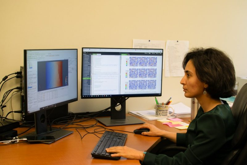 Maryam Shakiba sits at her desk while working on computational modeling on two computer monitors.