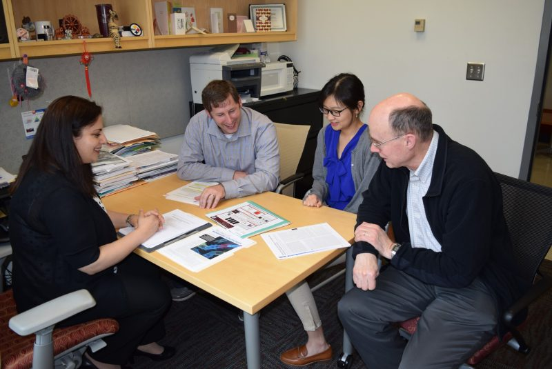 Several faculty members and a graduate student sit around a table as they discuss research.