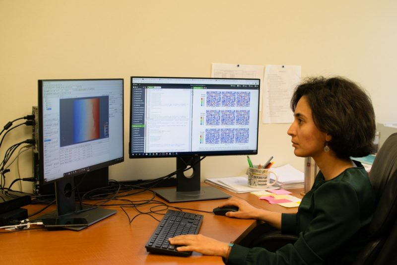 Maryam Shakiba sits at her desk looking at her dual monitors while working on computational modeling work.